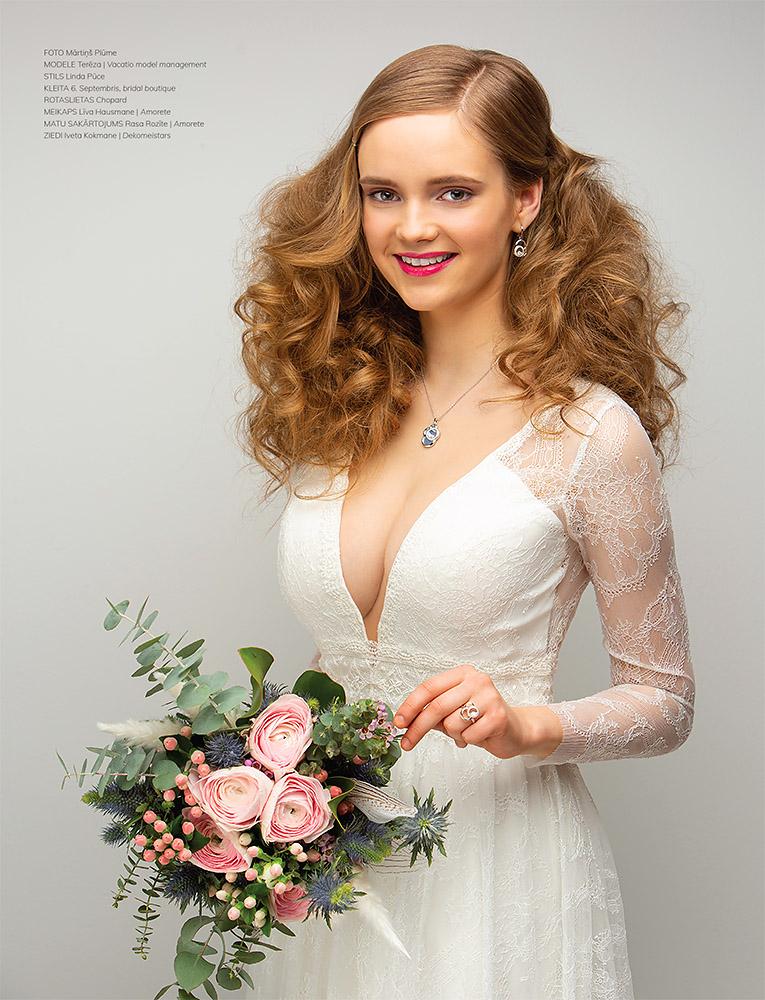 Rudmate ar lielām krūtīm baltā kāzu kleitā un dažādu ziedu pušķi rokās